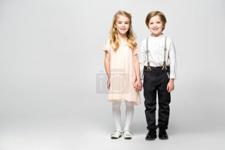 Foto de Smiling little boy and girl holding hands and looking at camera isolated on white - Imagen libre de derechos