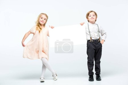 Foto de Happy little boy and girl holding blank card and smiling isolated on white - Imagen libre de derechos