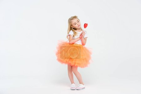 Photo pour Cute little girl in festive dress holding heart shaped lollipop  isolated on white - image libre de droit