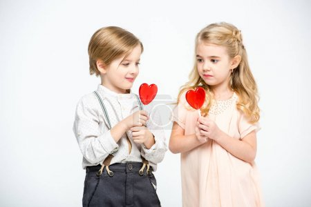Photo for Cute little boy and girl holding heart shaped lollipops  isolated on white - Royalty Free Image