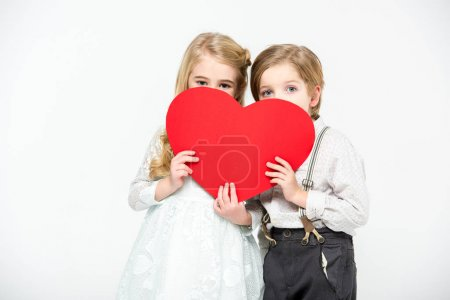 Photo for Two cute kids hiding their faces behind red paper heart isolated on white - Royalty Free Image