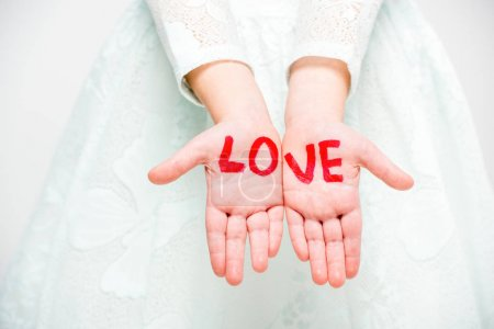 Photo for Close-up partial view of word love written on palms of child girl isolated on white - Royalty Free Image