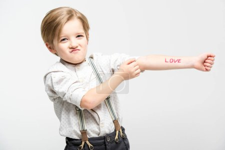 Foto de Cute little boy with word love written on his hand  isolated on white - Imagen libre de derechos