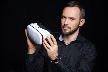 Photo for Bearded man holding virtual reality headset isolated on black - Royalty Free Image
