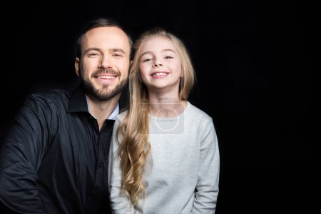 Photo pour Smiling father and daughter looking at camera  isolated on black - image libre de droit