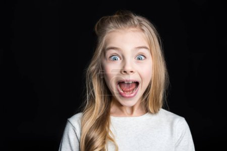 Photo pour Cute blonde girl screaming and looking at camera  isolated on black - image libre de droit