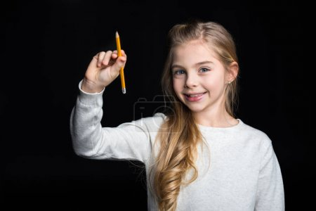 Photo for Cute blonde girl holding pencil and smiling at camera isolated on black - Royalty Free Image