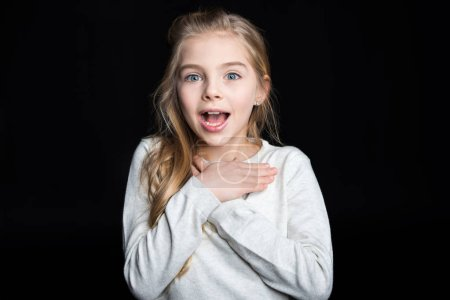 Photo for Cute surprised blonde girl looking at camera  isolated on black - Royalty Free Image