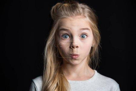 Photo for Cute preteen blonde girl grimacing isolated on black - Royalty Free Image