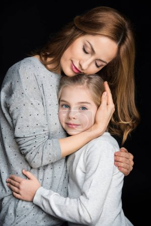 Photo for Beautiful mother and daughter hugging isolated on black - Royalty Free Image