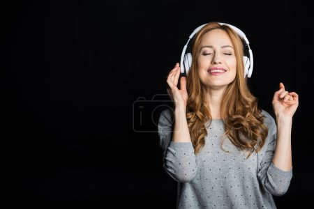 Photo pour Portrait of young woman in white headphones enjoying music  isolated on black - image libre de droit