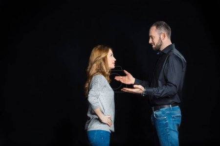 Photo for Young couple talking and looking at each other isolated on black - Royalty Free Image