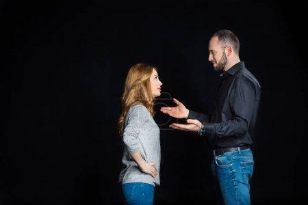 Photo pour Jeune couple parlant et se regardant isolé sur noir - image libre de droit
