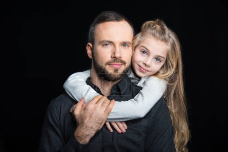 Photo for Portrait of smiling father and daughter hugging isolated on black - Royalty Free Image