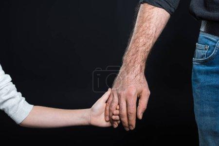 Photo pour Vue partielle du père et de sa petite fille tenant la main isolée sur du noir - image libre de droit