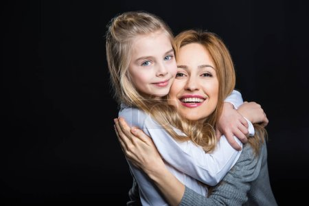 Photo for Young mother and her cute daughter embracing and smiling at camera  isolated on black - Royalty Free Image