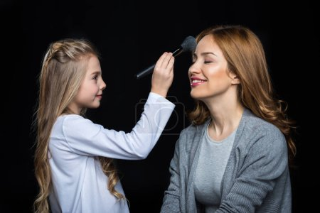Photo pour Little girl applying powder on her mother's face isolated on black - image libre de droit