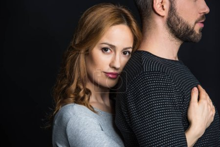 Photo for Young beautiful woman hugging her boyfriend from behind and looking at camera isolated on black - Royalty Free Image