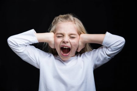 Photo for Little girl screaming and covering her ears with hands isolated on black - Royalty Free Image