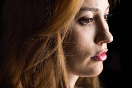 Photo for Close-up side view of serious young woman  isolated on black - Royalty Free Image