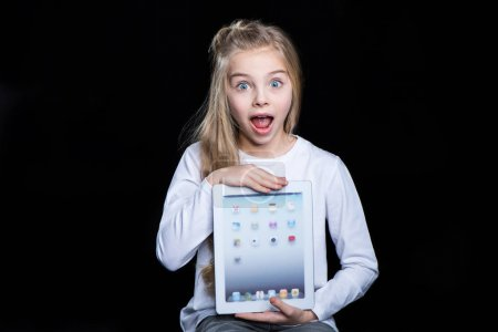 Photo pour Excited little girl holding digital tablet and looking at camera  isolated on black - image libre de droit