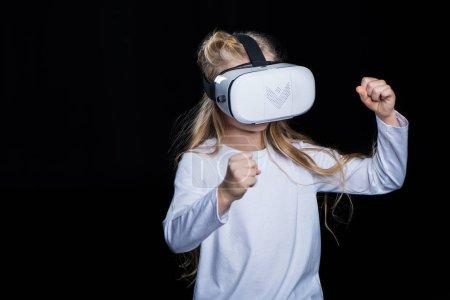 Foto de Little girl wearing virtual reality headset and gesticulating  isolated on black - Imagen libre de derechos