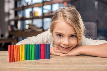 Photo pour Preteen blonde fille jouer avec coloré plasticine et sourire à la caméra - image libre de droit