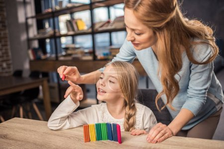 Mother and daughter playing with plasticine