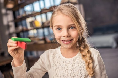 Photo for Cute preteen girl playing with plasticine and smiling at camera - Royalty Free Image