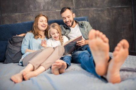 Photo pour Famille heureuse couché sur le lit et lire le livre ensemble - image libre de droit