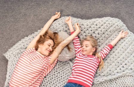 Photo for Top view of mother and daughter waking up and stretching themselves - Royalty Free Image