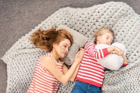Photo pour Vue du dessus de la mère et de la fille couchées sur une couverture en laine et dormant - image libre de droit