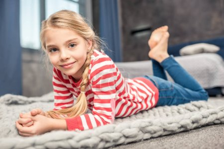 Photo for Pretty little girl lying on floor and smiling at camera - Royalty Free Image