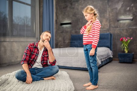 Photo pour Jeune papa en regardant sa fille tout en étant assis sur le sol dans la chambre - image libre de droit