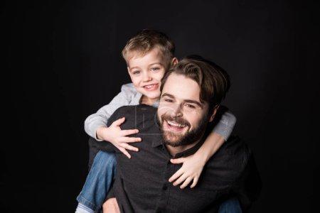 Photo pour Heureux père piggybackking mignon petit fils et sourire à caméra isolé sur noir - image libre de droit