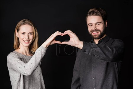 Photo pour Smiling young couple performing heart symbol with hands and looking at camera  isolated on black - image libre de droit