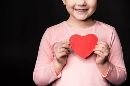 Photo for Partial view of cute little girl holding red paper heart  isolated on black - Royalty Free Image