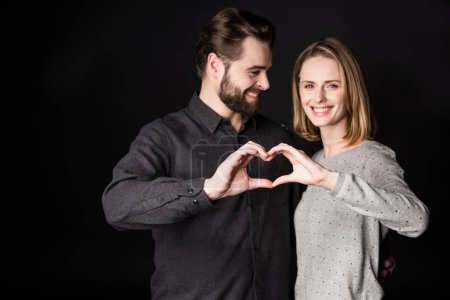 Photo pour Beautiful smiling young couple showing heart sign  isolated on black - image libre de droit