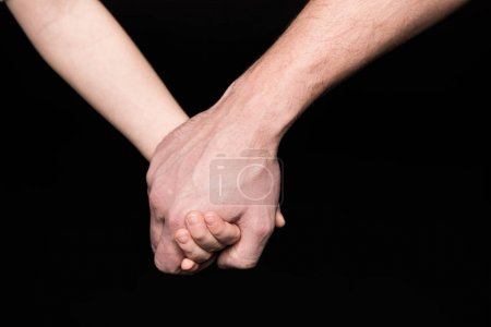 Photo for Close-up partial view of father and little child holding hands  isolated on black - Royalty Free Image