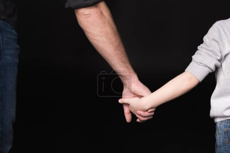 Father and child holding hands