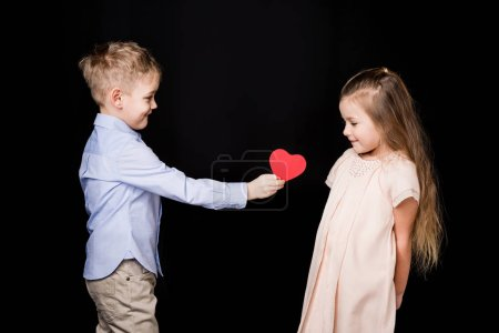 Photo for Cute smiling boy giving red paper heart to adorable girl isolated on black - Royalty Free Image