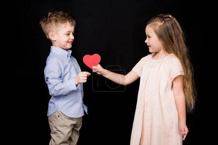 Photo pour Adorable petite fille donnant coeur de papier rouge au garçon souriant isolé sur noir - image libre de droit