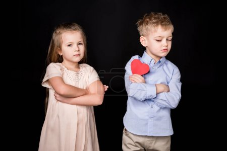 Photo for Two cute kids with arms folded standing with red paper heart  isolated on black - Royalty Free Image