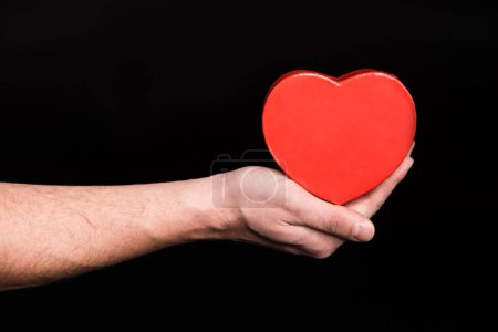 Photo for Close-up partial view of male hand holding heart sign  isolated on black - Royalty Free Image