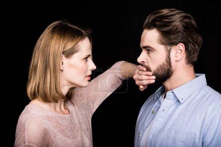 Photo pour Jeune femme couvre avec la bouche de la main du jeune homme isolé sur noir - image libre de droit