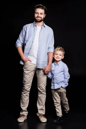 Photo for Young father and his little son holding hands and smiling at camera isolated on black - Royalty Free Image