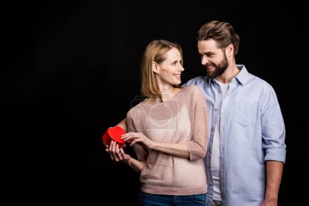 Photo for Happy young couple holding heart shaped gift and smiling at each other isolated on black - Royalty Free Image