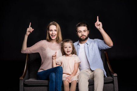 Photo for Young happy family of three sitting on sofa and pointing up  isolated on black - Royalty Free Image