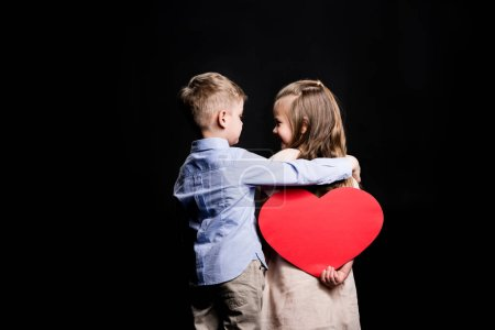 Photo pour Rear view of little boy hugging little girl who holding red paper heart isolated on black - image libre de droit