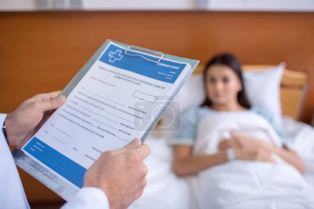 Photo for Close-up partial view of male doctor holding folder with documents - Royalty Free Image
